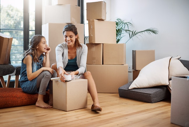 An attractive young woman and her daughter moving into a new house