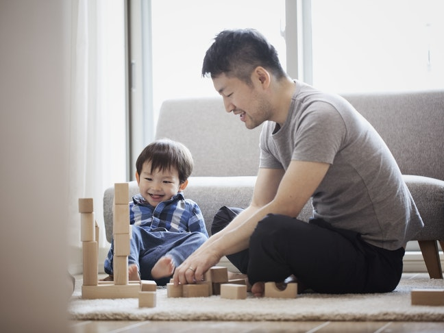 An Asian father and son playing with blocks sitting on floor
