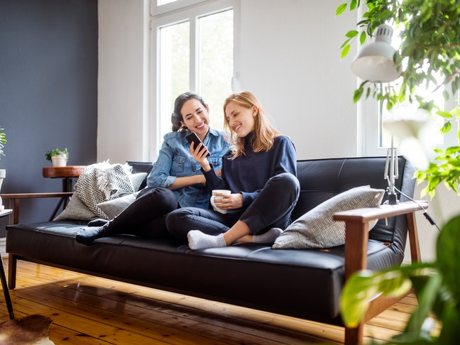 Happy young female friends sitting together on couch looking at a mobile phone