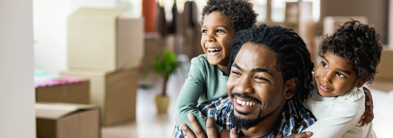 Happy African American kids embracing their single father at new apartment