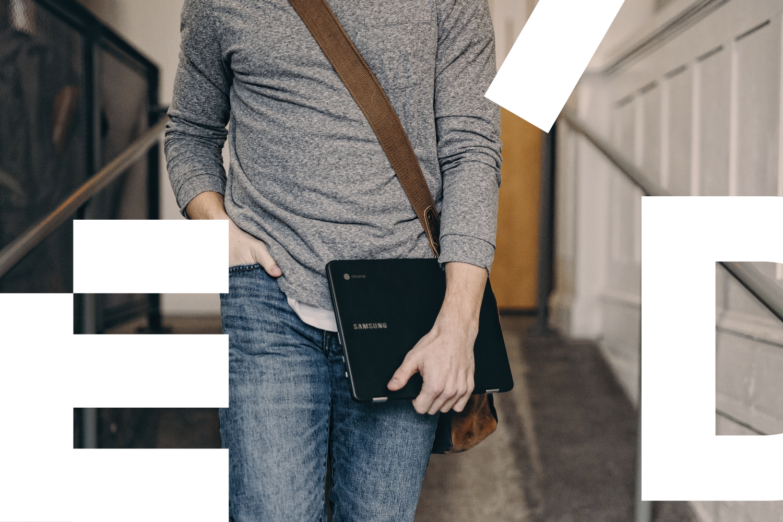 Mies kantaa tietokonetta.