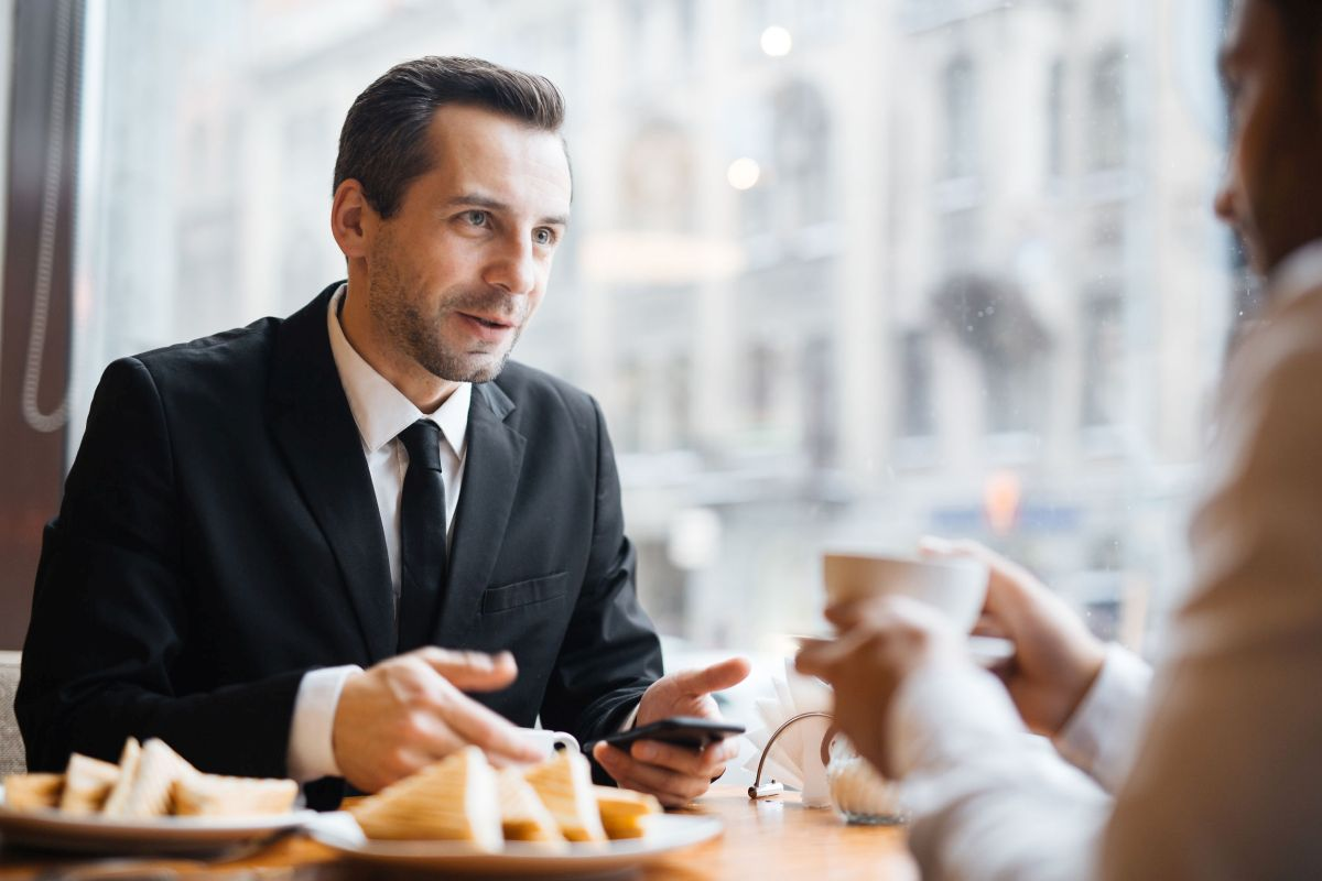 Portrait of two businessmen having discussion in warm lit cafe: brunette middle-aged gentleman talking to a man out of frame gesturing actively and smiling|fictitious 3d rendering of a modern living room with my own drawing|Young Military Couple Looking Inside Custom Kitchen and Design Drawing Combination.