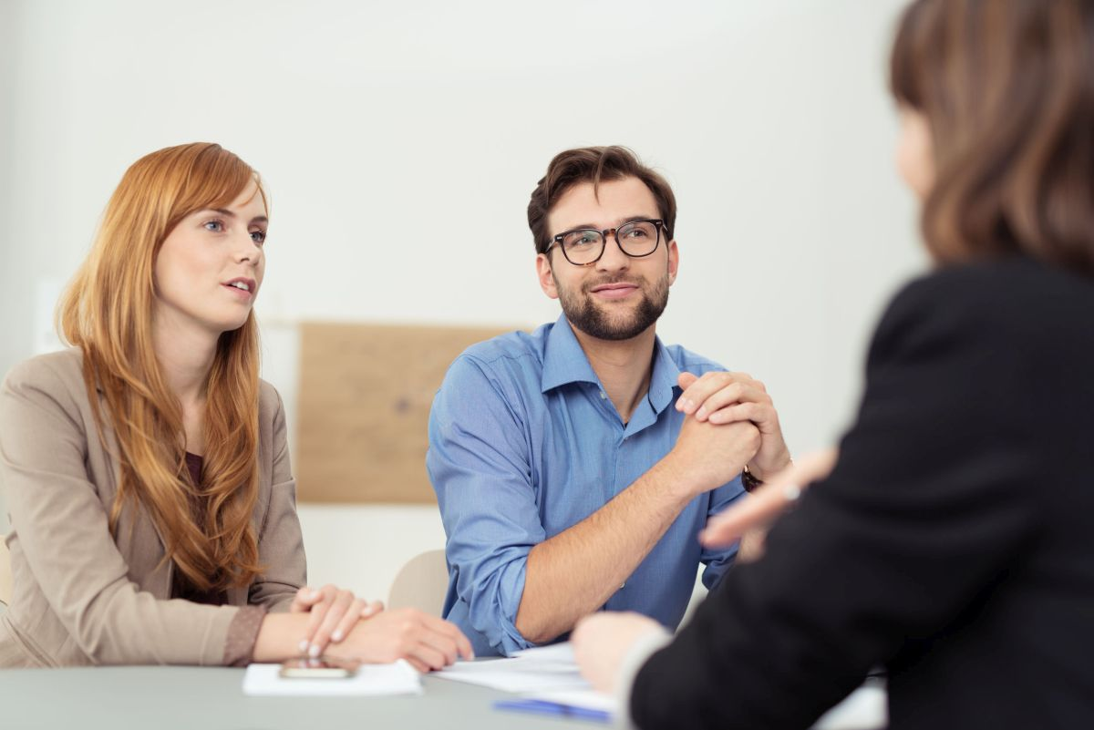 Broker having a discussion with a young couple who are sitting listening to her with serious attentive expressions|Insurance flow chart directions, business concept|Freelance operator working online