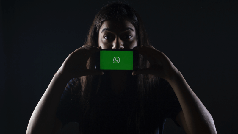 a person holding a phone with the WhatsApp logo on the screen