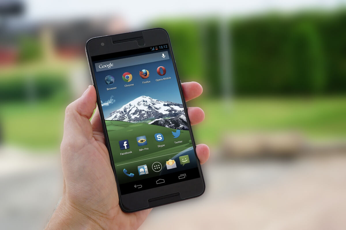 hand holding android phone with app icons showing
