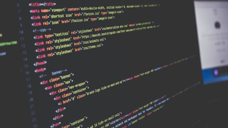 monitor with text editor open and HTML on screen