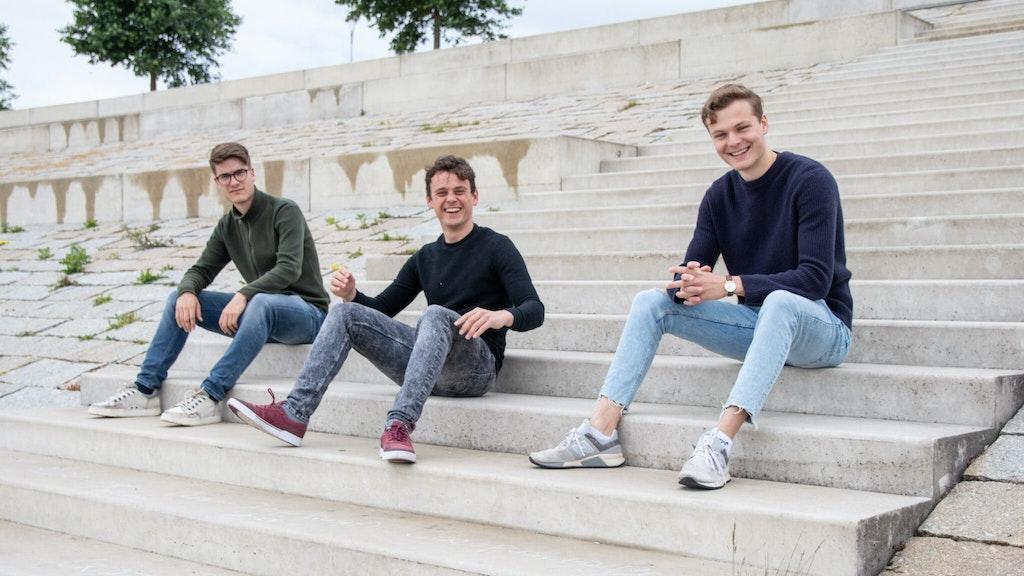 Drie jongens lachen en zitten op een stenen trap in de buitenlucht