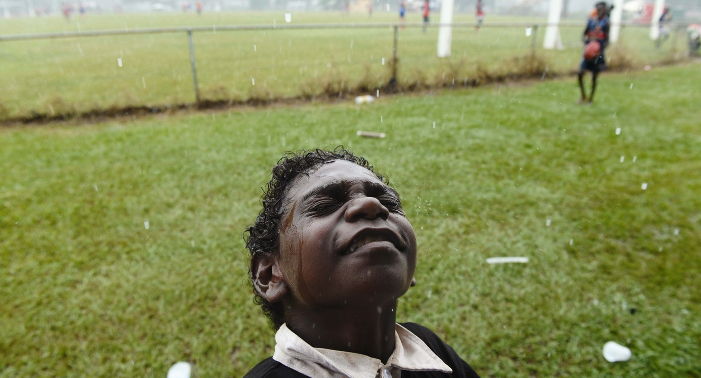 A young football fan feels the rain on his face minutes before kick-off for the Tiwi Islands grand final – the muddiest game of football.