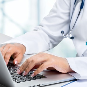 medical worker typing on laptop