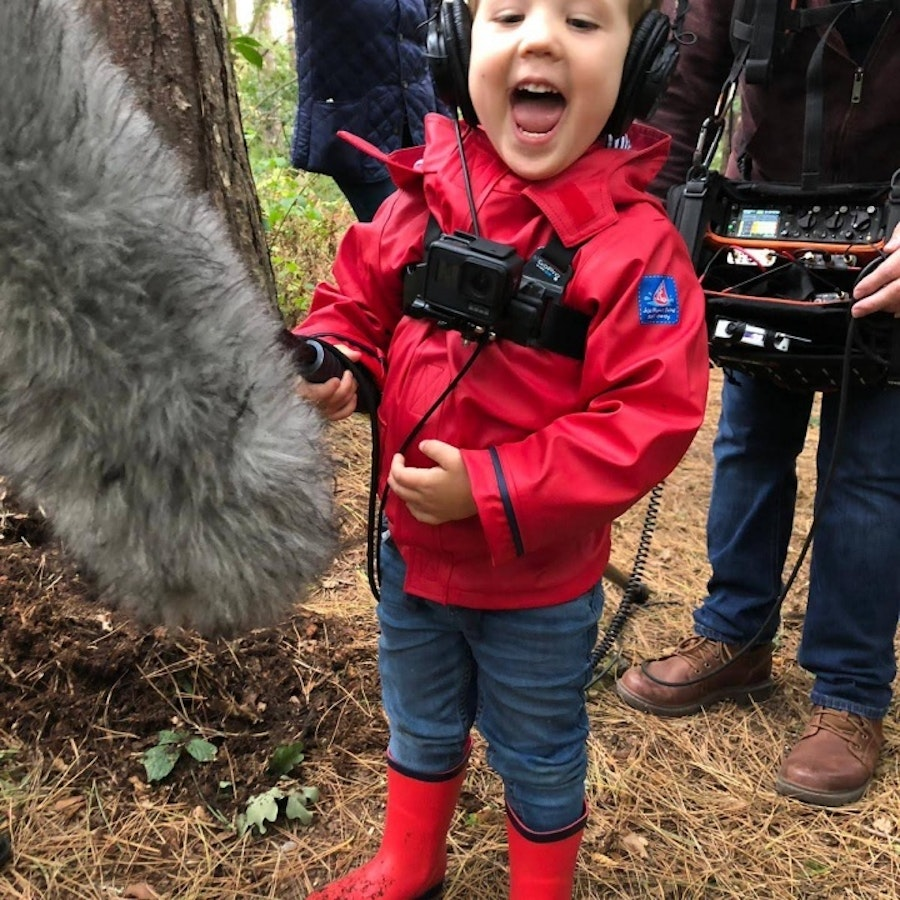 Toddler wearing red jacket and wellies holding a microphone in a forest