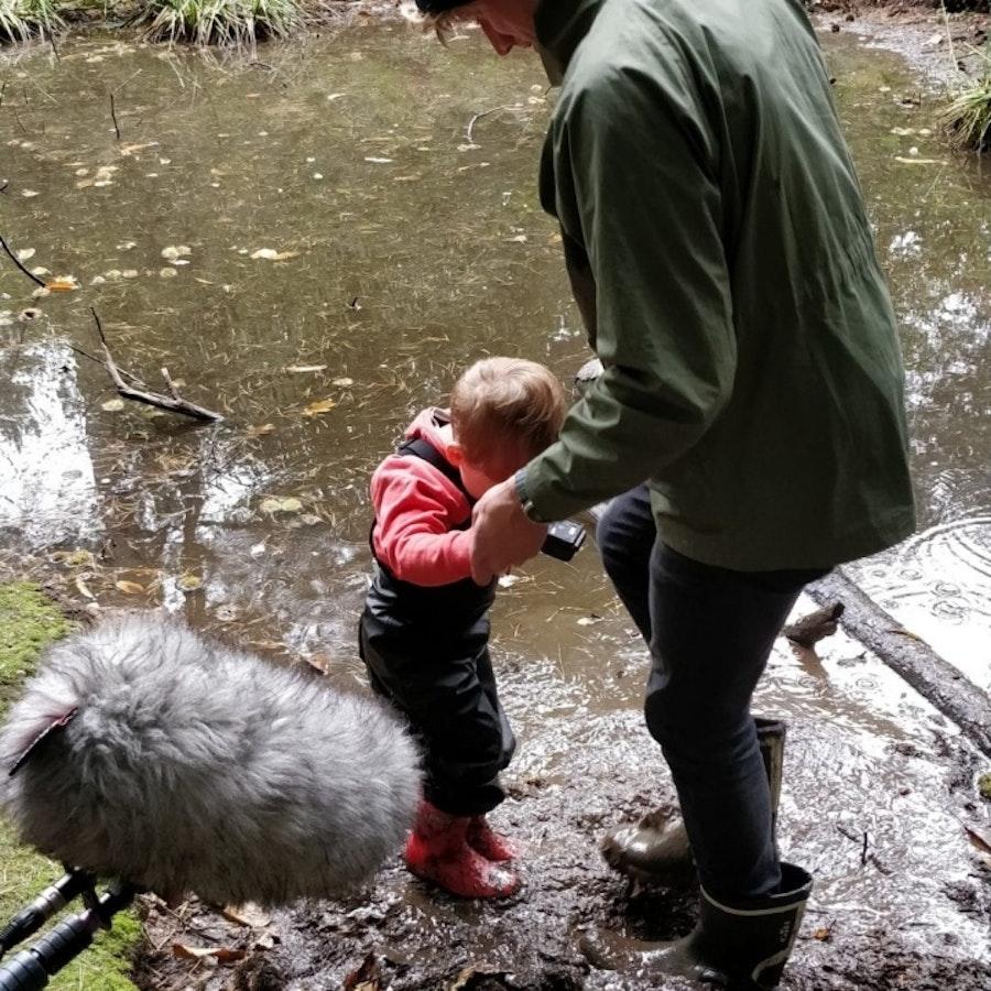 Man and toddler splashing in a puddle