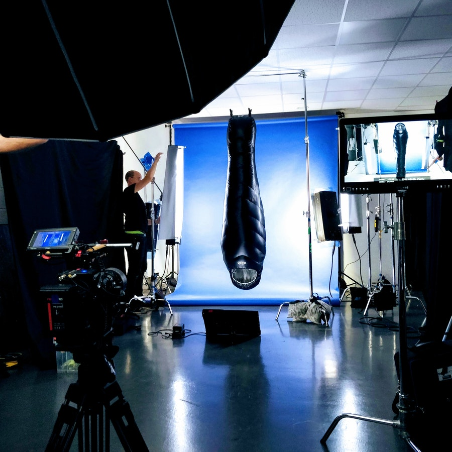 Rab Mythic Ultra Sleeping bag hung upside down on a film set, with blue screen in background