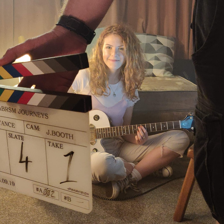 ABRSM Journeys BTS showing a female guitarist sat cross legged on the floor, looking at a tablet whilst studying guitar. The curtains are closed and a lamp lights the room.