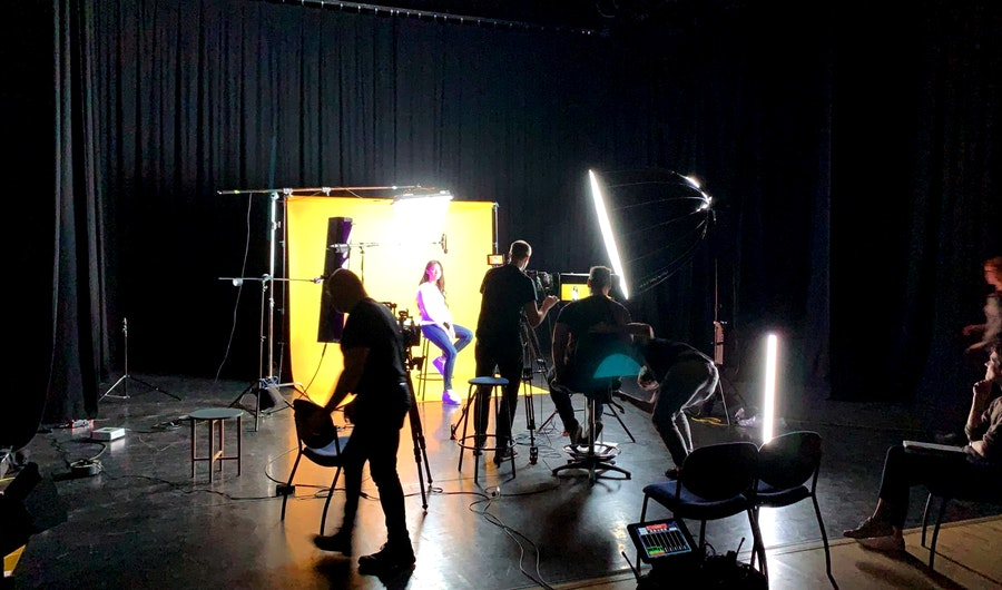 Image of a studio with a film crew featuring a student sat on a colorama background