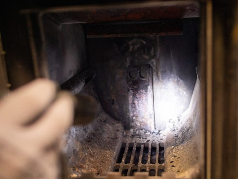 Checking the wood burning sauna heater with a  flashlight