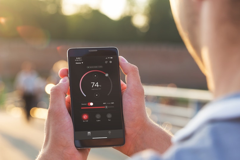 Man with adjusting MyHarvia app while jogging