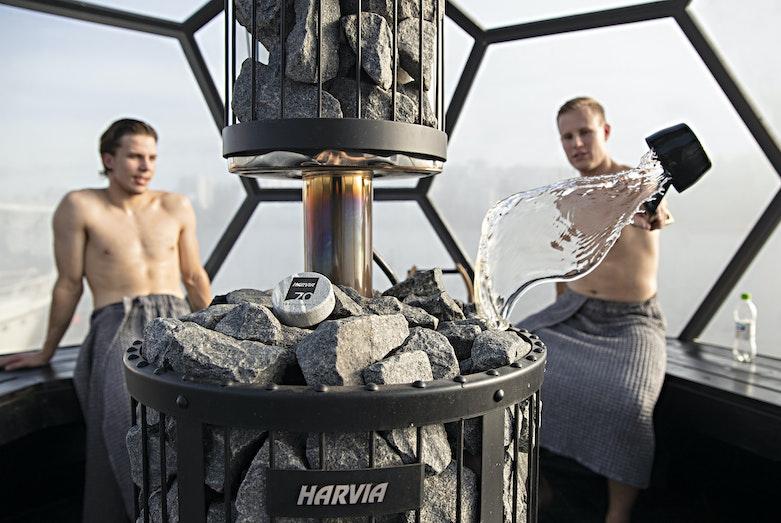 Men enjoying Harvia Legend GreenFlame woodburning heaters löyly