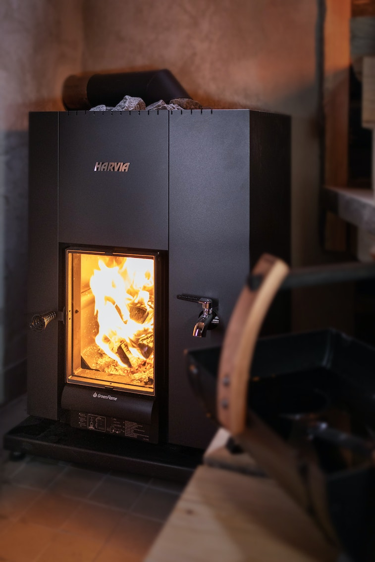 Harvia Linear 22 GreenFlame wood burning heater in a rustic sauna