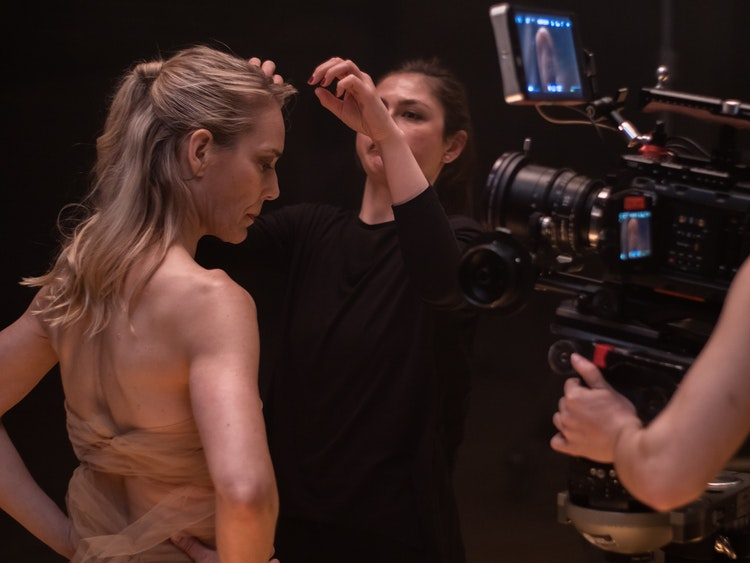 woman preparing performers hair during video-shoot