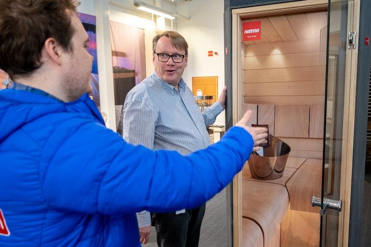 Man showing sauna doors to other man