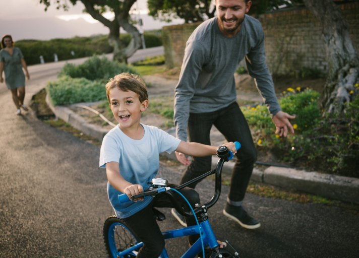 A photo of a father running after his son as he learns to ride a bicycle