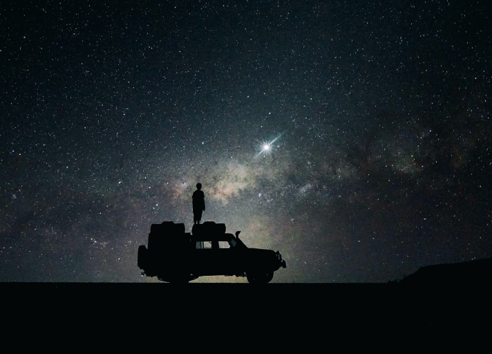 A long exposure photo of a nighttime starry sky and silhouette of a car and a person standing on the car