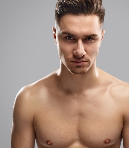 Handsome young male with muscular torso looking at camera while standing against gray background