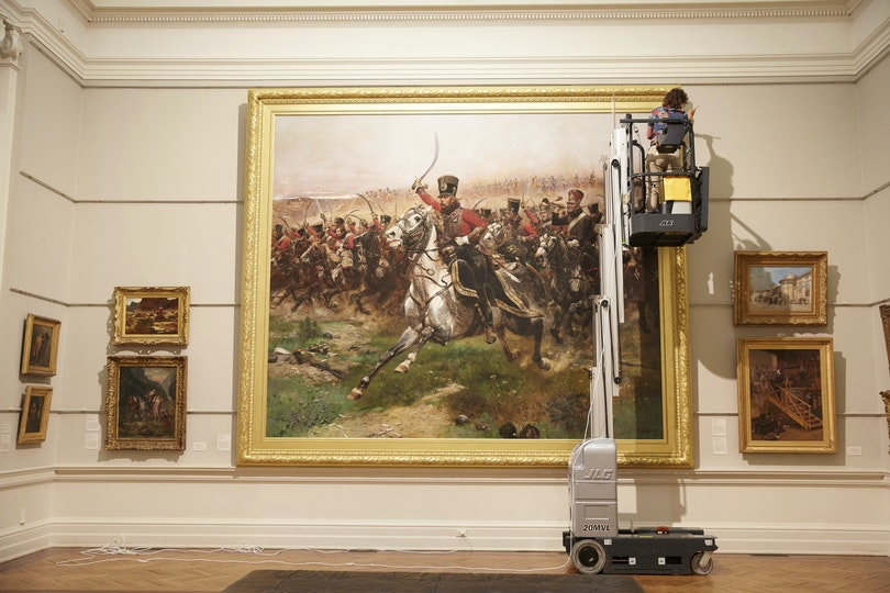 Conservator Melissa Harvey dusts the 1891 Édouard Detaille painting Vive L'Empereur! in the Old Courts.
