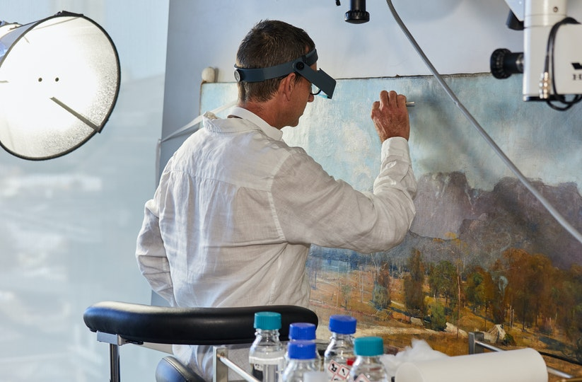 Paintings Conservator Simon Ives working on Arthur Streeton's 1894 painting, The Gloucester Buckets.