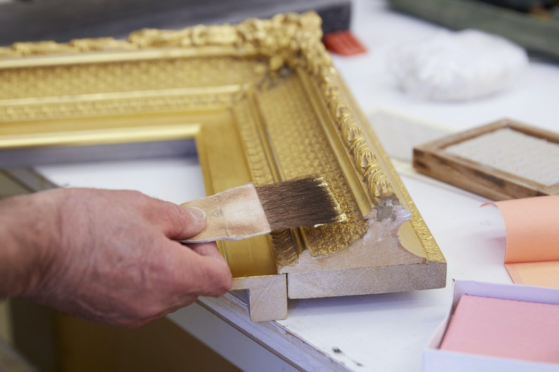 Gold leaf is applied to the frame using traditional gilding techniques.