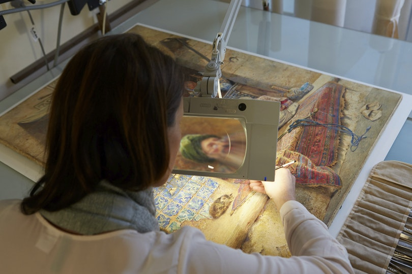 Paper conservator Analiese Treacy works on a c. 1886 watercolour, Bazaar gossip, by Charles Robertson.