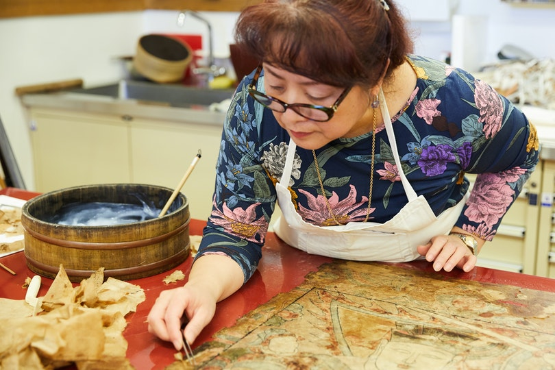 Asian art conservator Lily Yang working on the Gallery's fragile Yao ceremonial painting Taiwei, the high constable, 1857, for display in Walking with Gods. Conserving nine of these fragile works by Yao people (China) was an intricate process that took six months to complete.