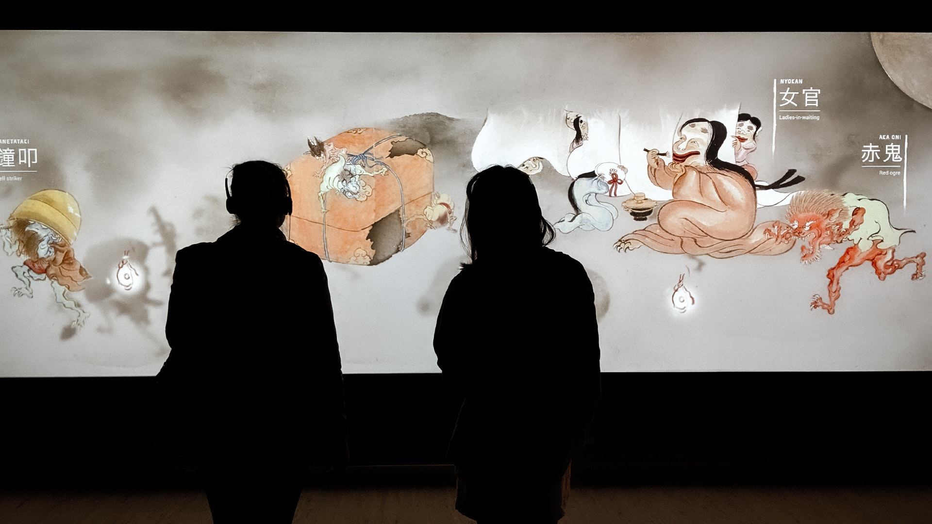 Visitors enjoying the Japan Supernatural interactive touch wall featuring characters from Hiroharu Itaya Night procession of one hundred demons circa 1820 (detail)