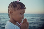 Video still of a child with clasped hands in front of the sea.