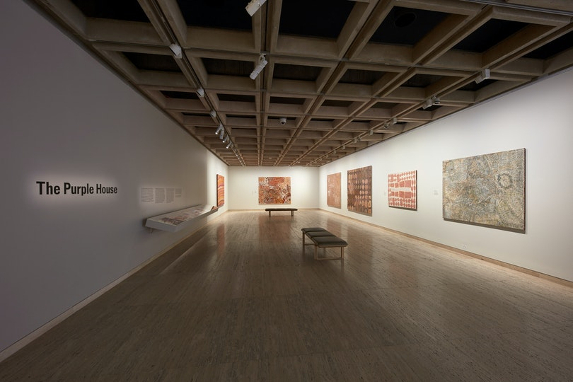 A gallery space hung with six Aboriginal paintings with 'The Purple House' written one one wall.