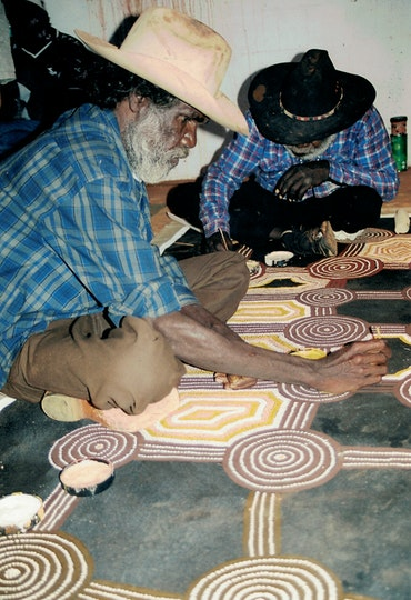 Two Aboriginal men sitting cross-legged on the floor on top of a large artwork that they are painting with small brushes.