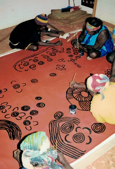 Four Aboriginal women on the floor on top of a large artwork that they are painting with small brushes.