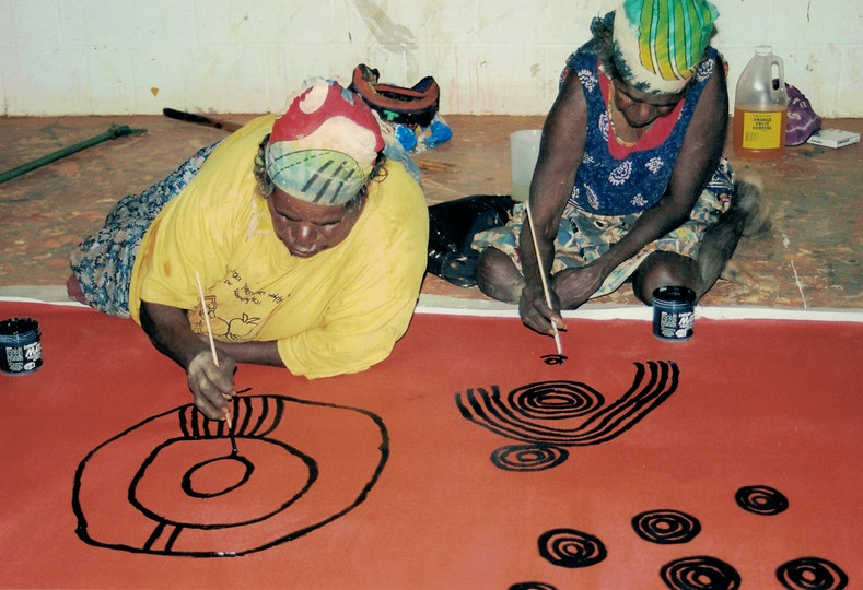 Two Aboriginal women on the floor on top of a large artwork that they are painting with small brushes.