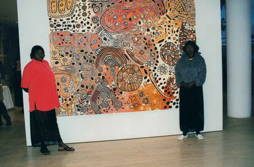 Two Aboriginal women stand with a large painting on a gallery wall.
