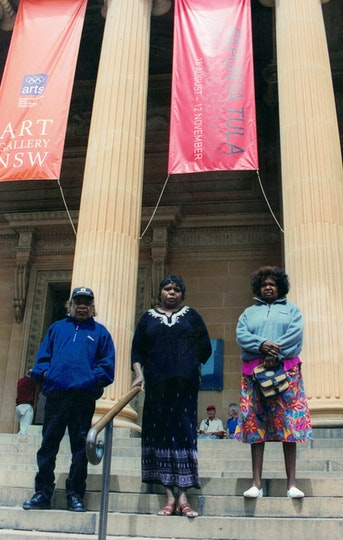 Three Aboriginal people stand on steps in front of tall columns, between which hang two banners. One banner has a logo consisting of the five Olympic rings with 'arts' written underneath, and a logo consisting of 'Art Gallery NSW'; the other says 'Papunya Tula Genius & Genesis 18 August - 12 November'..