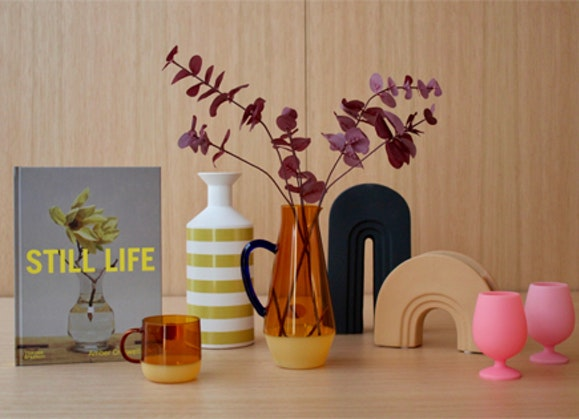 Book titled 'Still Life', orange glass mug, lime green and white striped vase, orange glass jug with black handle and dried leaves arranged in it, black book end and bright pink silicone wine globlets.