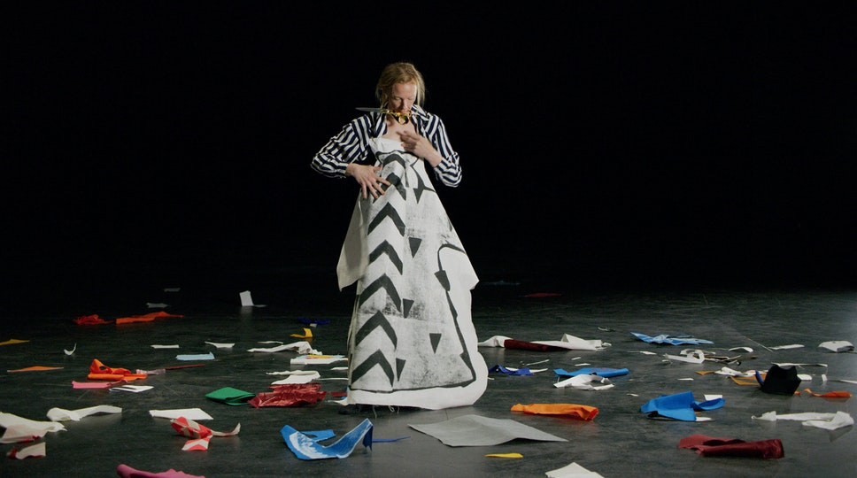 A person holds up a large piece of white paper with a black and grey pattern in front of their body. Scraps of coloured paper lie on the floor around them.
