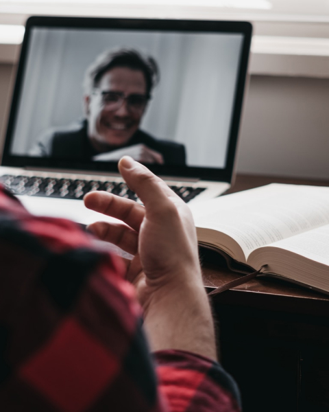 Photo représentant une séance de visioconférence. Au premier plan se situe l'épaule et la main d'un homme. Au second plan apparait un ouvrage papier ouvert et au troisème plan, un homme est visible à travers l'écran d'un ordinateur.