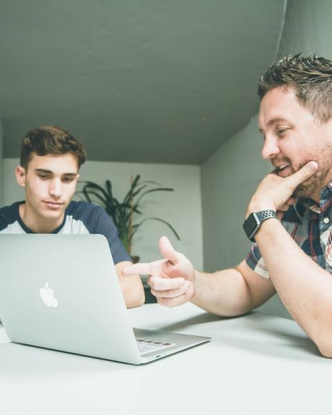 Cette photo représente une situation de travail et d'échanges entre deux hommes dans une pièce autour d'un ordinateur. A droite de l'image, un homme avec une main au niveau du menton, portant une montre au poignet, pointe du doigt l'ordinateur de l'autre main en expliquant quelque chose à l'autre homme plus jeune à côté de lui à 90 degré.  Au second plan, le second homme regarde l'ordinateur en étant attentif aux explications du premier homme. Au troisième plan apparait une plante dans la pièce où a lieu la scène.