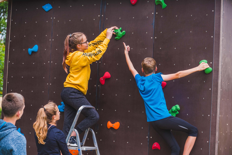 Zwei Mädchen und zwei Jungen bauen einen Boulderzusammen