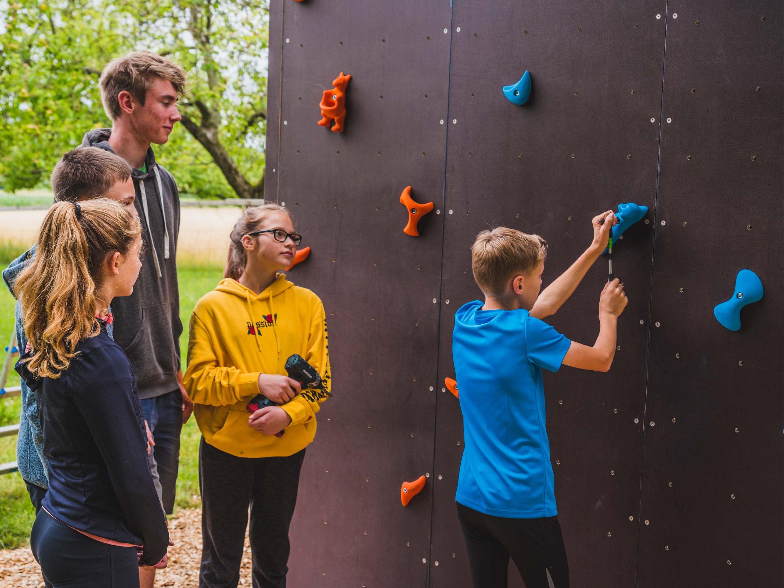 Ein Trainer baut mit jungen Menschen eine Route