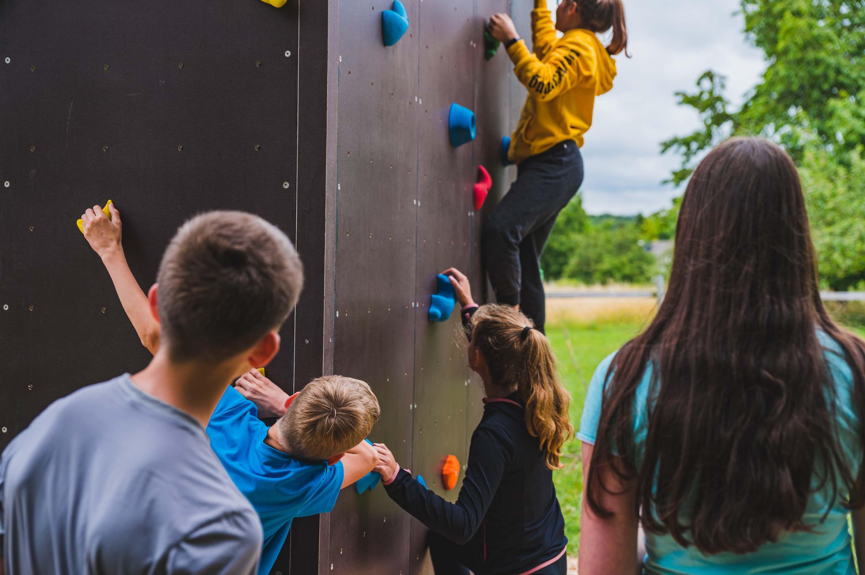 Junge Menschen Bouldern und geben einander Tipps