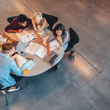 Vijf mensen rond een vergadertafel kijken naar het scherm van een laptop