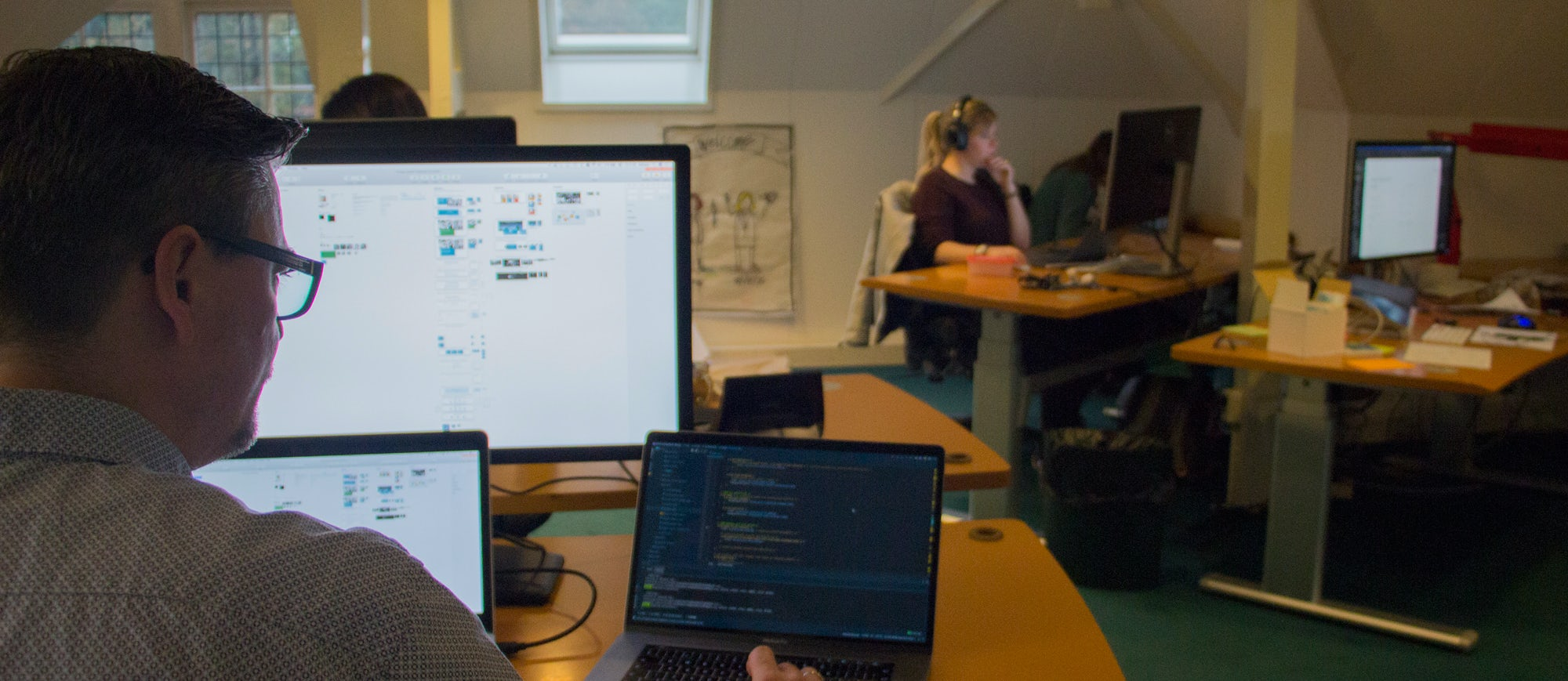 Een man achter drie beeldschermen in een kantoor-omgeving