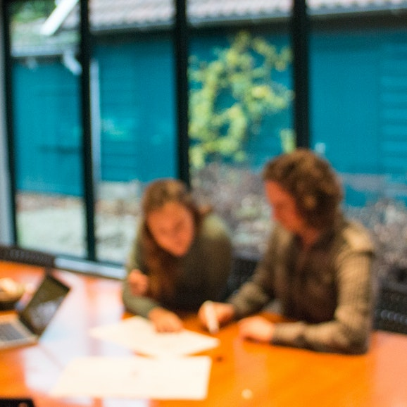Drie mensen aan tafel in een vergaderzaal